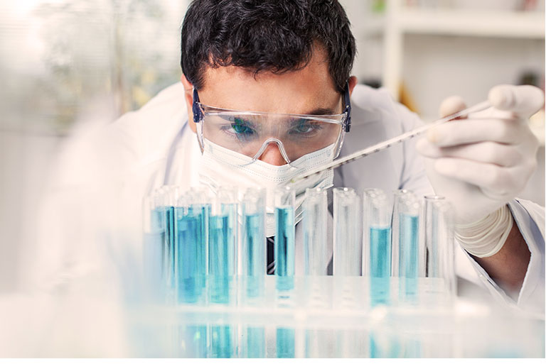 Lab technician filling test tubes